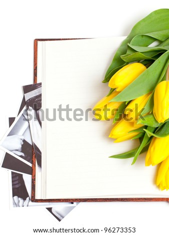yellow tulips lying on book with black and white photographs - stock photo