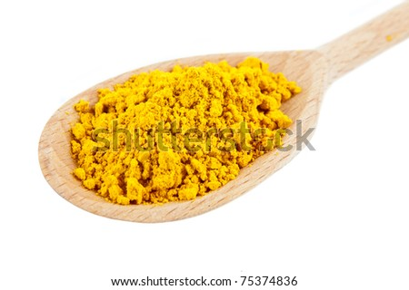 Yellow tumeric spice on wooden spoon over white background