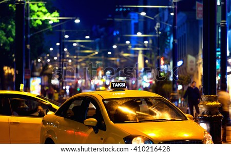 Yellow turkish taxi car with colourful bokeh of city lights - stock photo