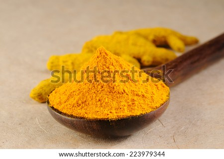 yellow turmeric in wooden spoon,Ground turmeric on wooden spoon and turmeric roots  - stock photo