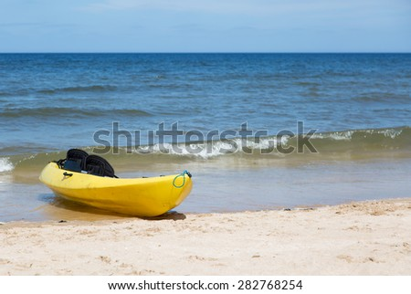 Yellow two seat kayak on a sandy beach - stock photo
