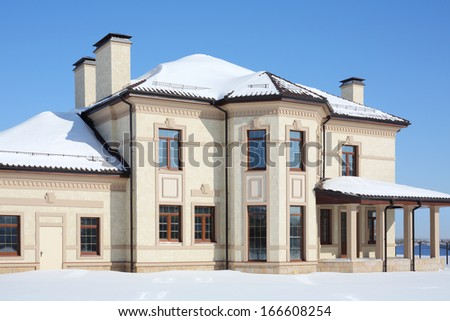 Yellow two-storey new cottage with porch on sunny frosty winter day. - stock photo