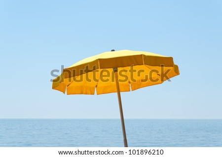 yellow umbrella over sea under blue sky - stock photo