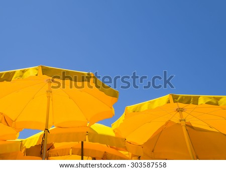 Yellow umbrellas - blue sky. Summer background.