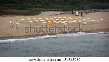 Yellow umbrellas on a beach, high angle, Bulgaria - stock photo