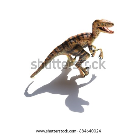 yellow velociraptor toy on a white background with shadow