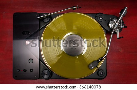 Yellow vinyl record played on a hi-end turntable record player top view standing on red wood stand - stock photo