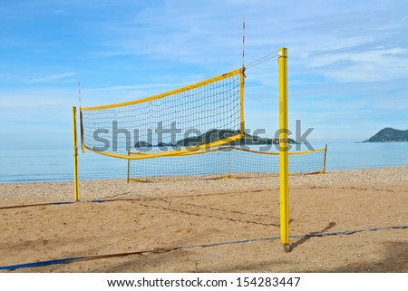 Yellow volleyball net and post on the beach