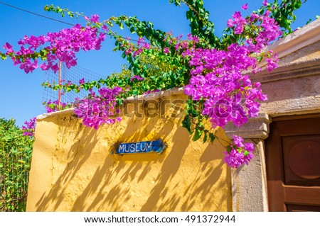 yellow Wall with museum sign and pink flowers, blue sky. Greece, Crete, Symi.