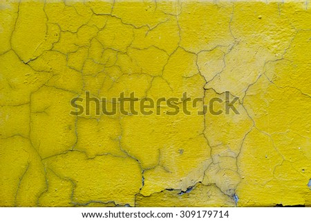 yellow wall with the whitewash falling off fragment as a background texture - stock photo