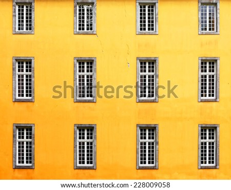 Yellow wall with windows - stock photo