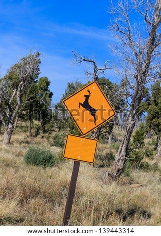 Yellow warning road sign of a deer leaping, warning of wild deer on the road. Sign is placed in front of winter trees and grass. The lower rectangle sign has been made blank for your own message. - stock photo