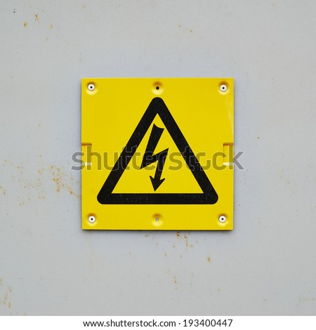 Yellow warning sign on a gray wall composition