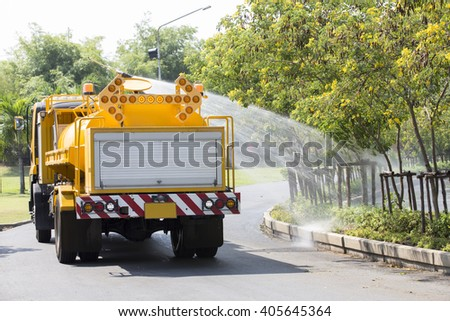 Yellow Water Tanker Watering Trees in a Garden