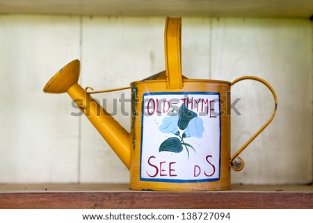 yellow  watering can in garden - stock photo
