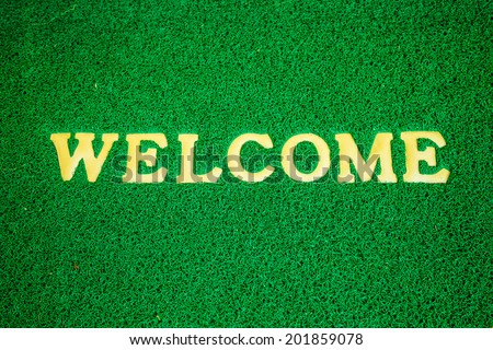 yellow welcome carpet, welcome doormat carpet - stock photo