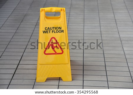 Yellow Wet Floor Sign Warning Of Slippery - stock photo