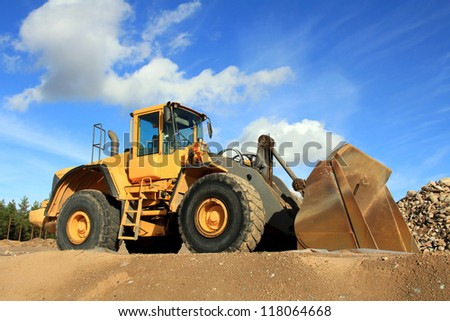 Yellow wheel loader at sand pit against blue sky. - stock photo
