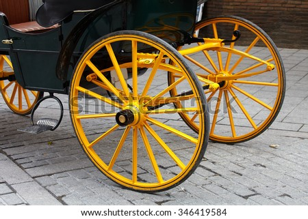 Yellow wheel olden horse carriage on the cobblestones Spain. Sevilla - stock photo