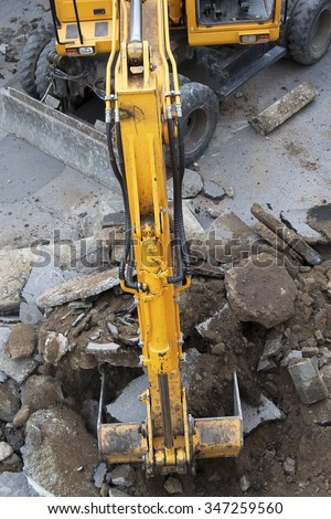 Yellow wheeled excavator removes dirt, asphalt and gravel on construction site.  - stock photo