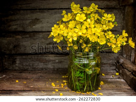 Yellow wildflowers collected in a bouquet on a rustic  background
