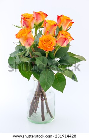 Yellow with red roses in a vase isolated on white - stock photo