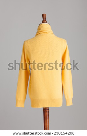 yellow woman cashmere sweater with wood model on grey isolated - stock photo