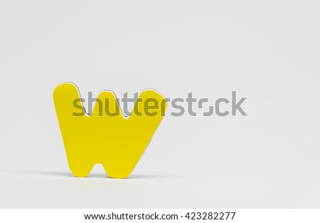 Yellow wooden alphabet W with white background and selective focus