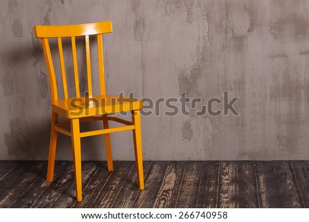 Yellow wooden chair in nterior room with gray decorative plaster wall and dark wooden floor - stock photo