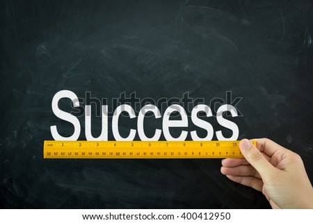 Yellow wooden ruler measures the word  success on blackboard - stock photo