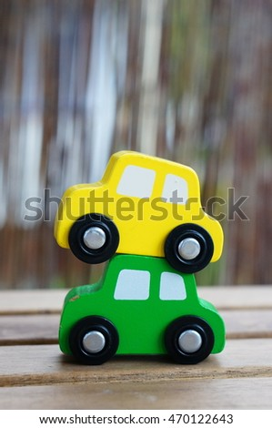 Yellow wooden toy car on green car on wooden table