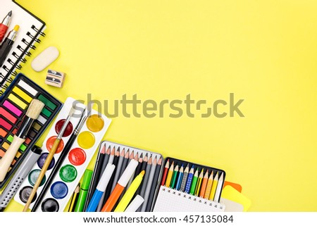 yellow writing desk with colorful stationary and office supplies for education process