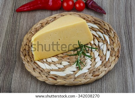 Yellow young cheese with pepper, rosemary and tomatoes