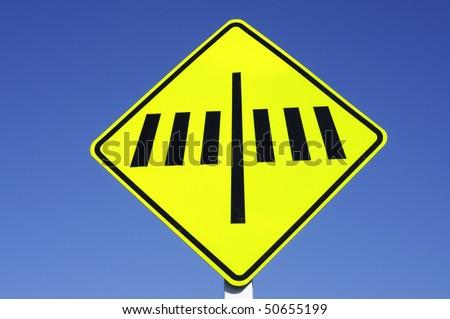 yellow Zebra crossing sign set against blue sky - stock photo