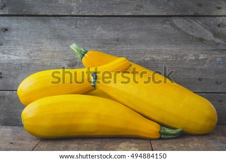 Yellow zucchini on a wooden background