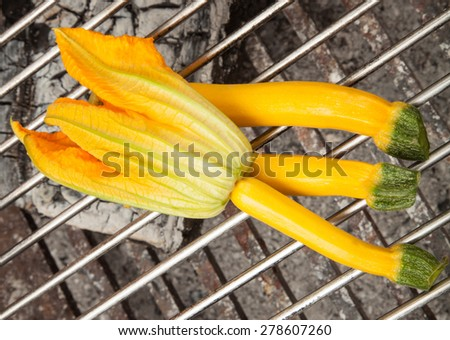 Yellow zucchini with blossoms on grill