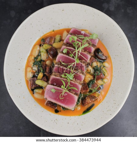 Yellowfin tuna with white beans, spanish chorizo, baby kale and clam butter - stock photo