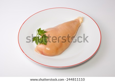 Yellowish chicken breast isolated over white background. Yellow coloring come from chicken fed with corn grains - stock photo