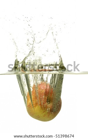 Yellowish red apple splashing in water with bubbles in white background - stock photo