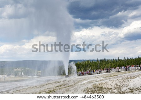 YELLOWSTONE NATIONAL PARK - JULY 26: Tourists enjoys Beehive Geyser eruption at Upper Geyser Basin on July 26,2016 in Yellowstone National Park