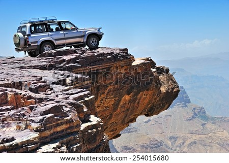 YEMEN - MARCH 13, 2010: Off-road vehicle on the edge of a steep cliff over breakaway at plateau Bokur (800m high). Extreme mountain safari is one of the main local tourist attraction in Yemen - stock photo
