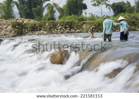Yen Bai, Vietnam - Sept 27, 2014: Ethnic people cross dangerously a rush stream in flooding season