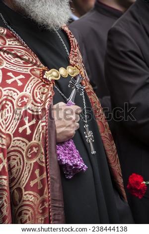 YEREVAN, ARMENIA - APRIL 24: Hands of an Armenian priest holding a cross at the Armenian genocide commemoration day in Tsitsernakaberd, YEREVAN, ARMENIA - stock photo