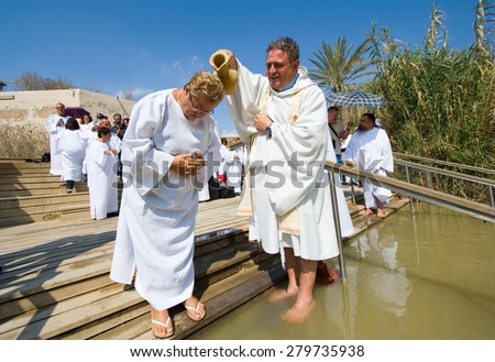 YERICHO, ISRAEL - OCT 15, 2014: A christian woman is being baptized by water during a baptism ritual at Qasr el Yahud near Yericho on the Jordan river - stock photo