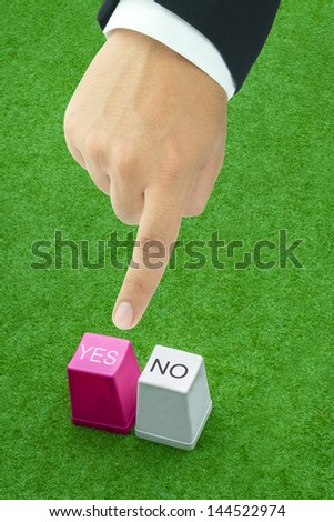 Yes and No buttons from keyboard on fake grass, with man's finger pressing one of them, concept of decision making - stock photo