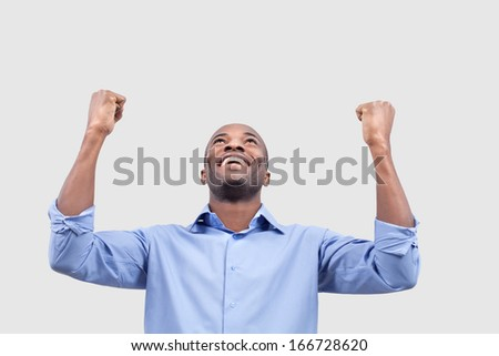 Yes! Cheerful young black man smiling and keeping arms raised while standing isolated on grey background