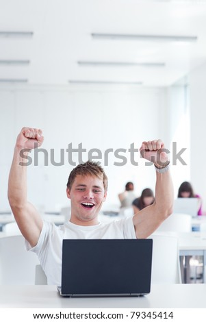 Yes! - happy young male college student, rejoicing over his success while working on his laptop computer in a study room (color toned image) - stock photo