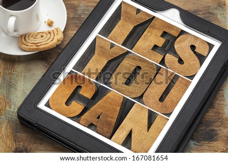 Yes you can - motivational slogan on a digital tablet with a cup of coffee - stock photo