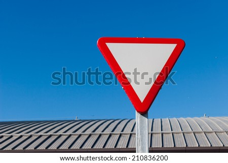 Yield - Give a way sign against blue sky - stock photo