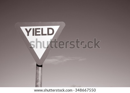 Yield Sign against a Sky Background in Black and White Sepia Tone